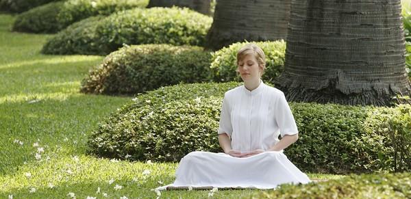 žena medituje v parku