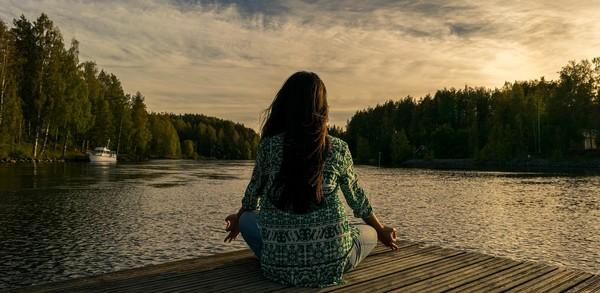 žena medituje pri jazere