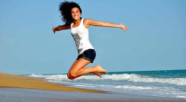 žena vo výskoku na pláži