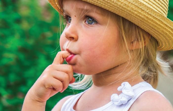 dievčatko si oblizuje prst